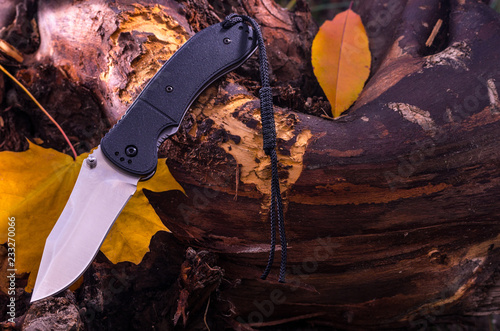 Tourist knife with lanyard. Autumn mood. Front view.