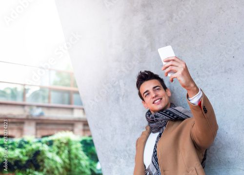 Fotografía  Outdoor portrait of modern young man with mobile phone in the street making a se