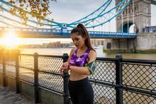 Attraktive, Sportliche Frau Nach Dem Fitness Workout Prüft Ihren Fortschritt Auf Der Uhr Bei Sonnenaufgang In Der Stadt, London, UK