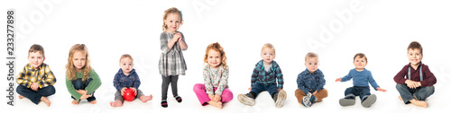 Fotografiet  A Group of child and baby sitting on white studio background