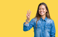 Young Beautiful Brunette Woman Wearing Blue Denim Shirt Over Isolated Background Showing And Pointing Up With Fingers Number Three While Smiling Confident And Happy.