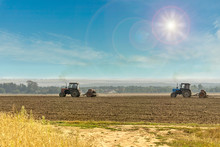 Old Tractors With Seeders On Beautiful Sunny Agricultural Landscape. Farmers Are Sowing Winter Wheat In Autumn. Toned With Lens Flare.