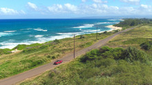 AERIAL: Red Convertible Driving Along The Coastal Road In Green Hawaii Island