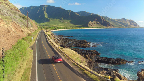 Poster Bleu AERIAL: Couple in red convertible car driving along the beautiful coastal road