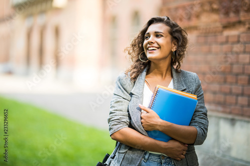 Fotografia Pretty cheerful latin american student smiling at camera carrying notebook on ca