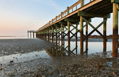 Overview of beautiful fishing pier at sunrise at low tide at Walnut Beach, Milford Connecticut, USA.
