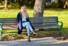 Beautiful Girl Sitting On Bench In Autumn In The Park