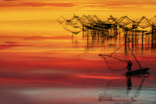 Silhouette Of Fisherman Fishing With Net On Boat With Background Of Thai Traditional Fishing Trap