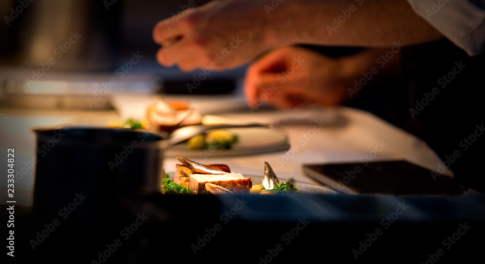 Fototapety, obrazy: Chef preparing a plate made of meat and vegetables. The chef is adding condiments to the plate