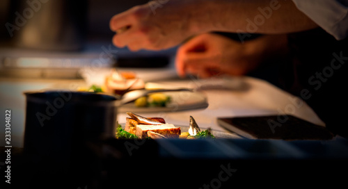 Fototapeta Chef preparing a plate made of meat and vegetables. The chef is adding condiments to the plate obraz