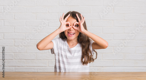 Fotografía Young hispanic kid sitting on the table at home doing ok gesture like binoculars sticking tongue out, eyes looking through fingers
