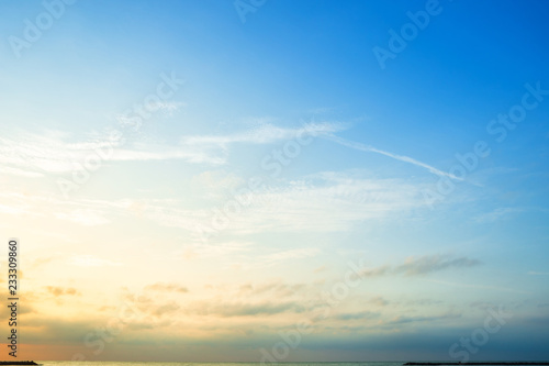 Obraz Beautiful early morning sunrise over the sea the horizon,blue sky background texture with white clouds sunset. - fototapety do salonu