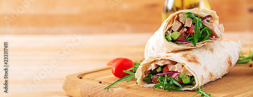Fotografering  Tortillas wraps with chicken and vegetables on  wooden background