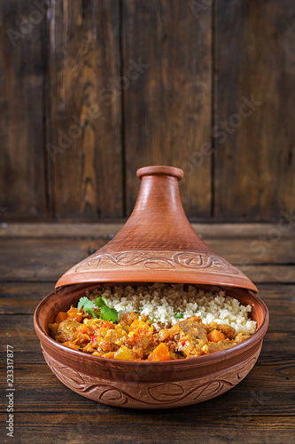 Fotomural Traditional tajine dishes, couscous  and fresh salad  on rustic wooden table