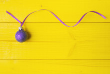 Christmas Ball With Long Curly Ribbon On Yellow Background.