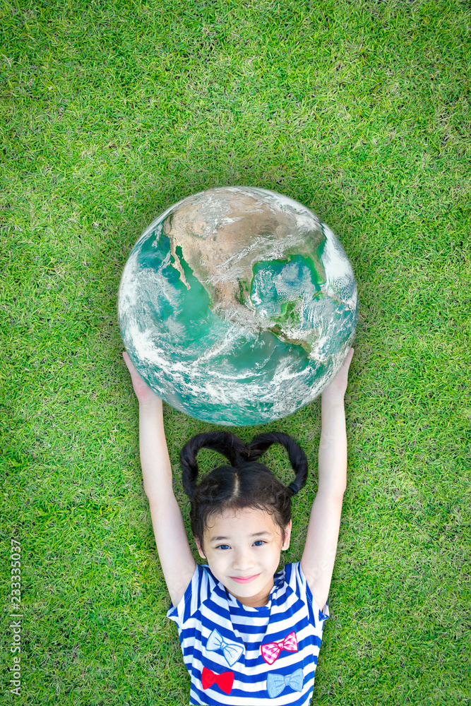Fototapeta Ecology CSR concept with happy kid raising green globe on eco friendly green grass lawn. Element of image furnished by NASA