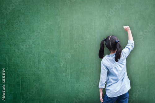 Fotografie, Obraz  Green classroom chalkboard background with student kid back view writing on boar