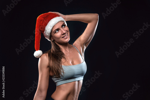 Fotografía  Attractive fitness woman is standing in christmas hat and looking upward