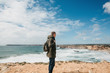 A tourist or traveler with a backpack on the Atlantic coast in Portugal.