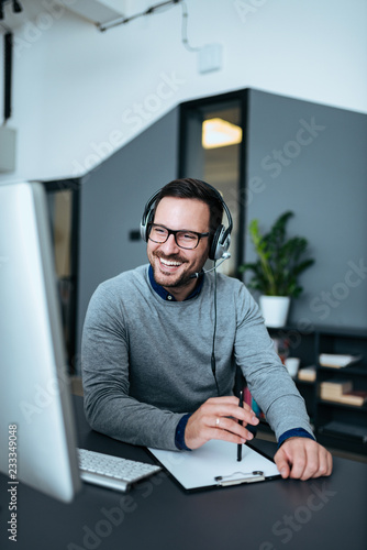 Photo Happy handsome tech manager talking with client on headset.
