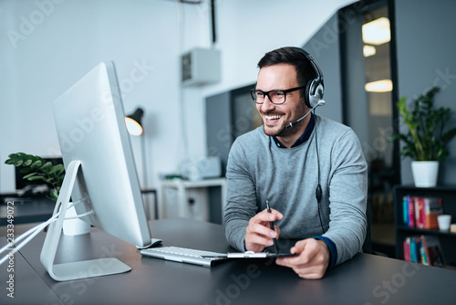 Portrait of a casual smiling businessman using headset when talking to customer.