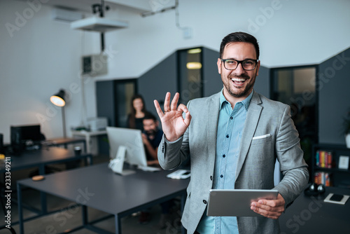 Fototapeta Handsome young businessman showing OK gesture in modern office. Colleagues in the background. obraz