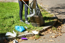 Woman Gathering Trash In Park