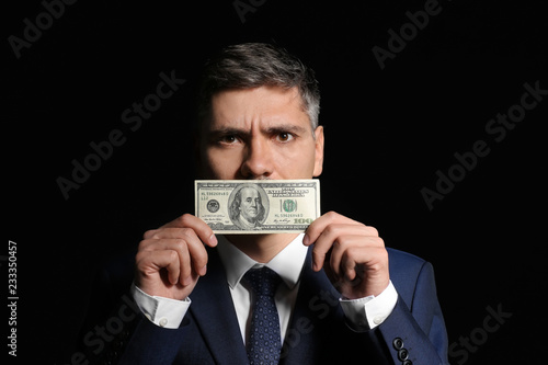 Businessman covering mouth with bribe on dark background Canvas-taulu