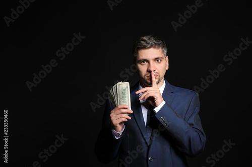 Businessman with bribe showing silence gesture on dark background Canvas-taulu