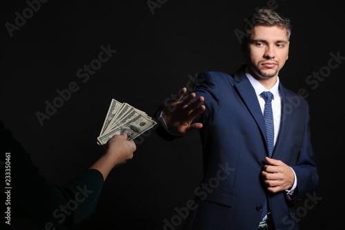 Valokuvatapetti Businessman refusing to take bribe on dark background