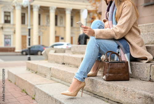 Fotografia  Beautiful fashionable woman with mobile phone sitting on steps outdoors