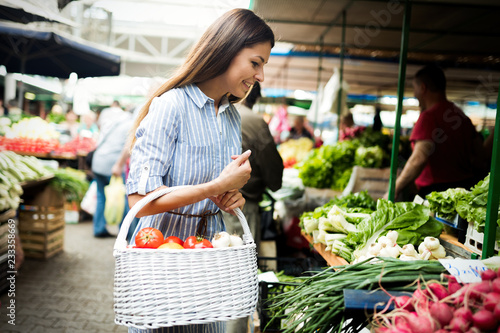 Young woman buying vegetables at the market. Fototapeta