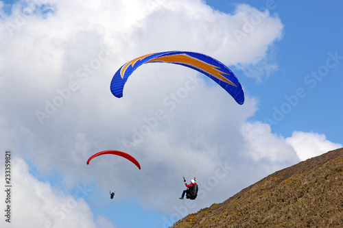Paragliders flying along a ridge