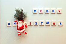 Funny  Santa Figurine, Red And Blue Letters Merry Christmas On White Background. New Year Concept