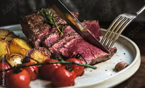 Woman eating a rare rib eye steak