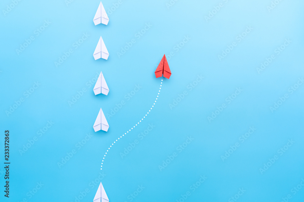 Fototapeta Group of white paper plane in one direction and one red paper plane pointing in different way on blue background. Business concept for new ideas, creativity, innovation and solution.