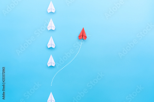 Obraz Group of white paper plane in one direction and one red paper plane pointing in different way on blue background. Business concept for new ideas, creativity, innovation and solution. - fototapety do salonu