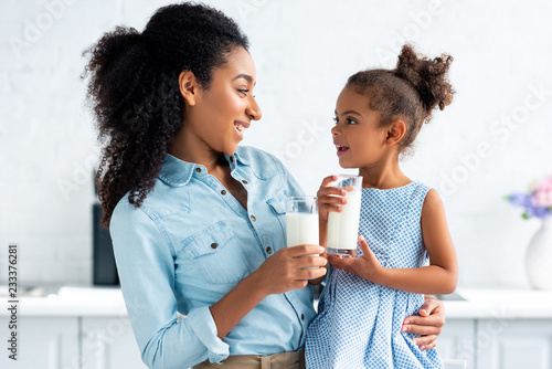 Papel de parede cheerful african american mother and daughter holding glasses of milk in kitchen