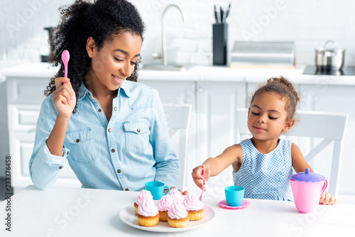 african american mother and daughter eating homemade cupcakes in kitchen Canvas Print