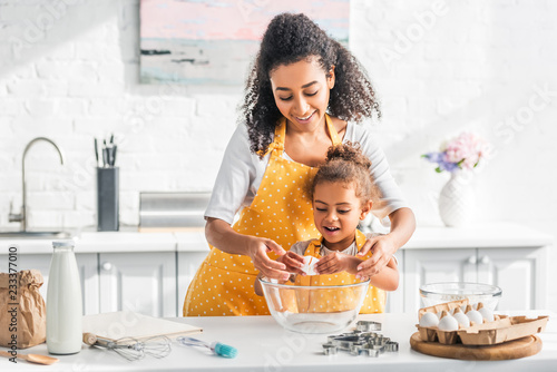 Fotografia smiling african american mother helping daughter breaking egg for preparing doug