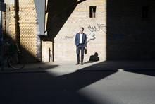 Businessman Standing At Graffiti Wall Looking Around