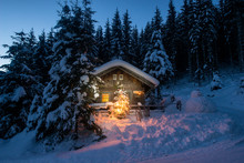 Illuminated Wooden House With Snowman And Christmas Tree On Snowy Landscape