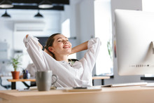 Happy Young Woman Dressed In Shirt Sitting At Her Workplace