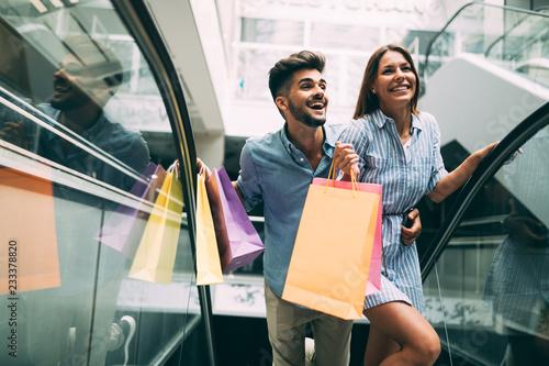 Obraz na plátně Happy attractive loving couple enjoy shopping together