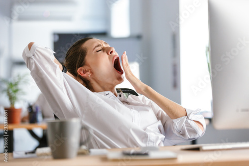 Fotografie, Obraz  Sleepy young woman dressed in shirt sitting at her workplace