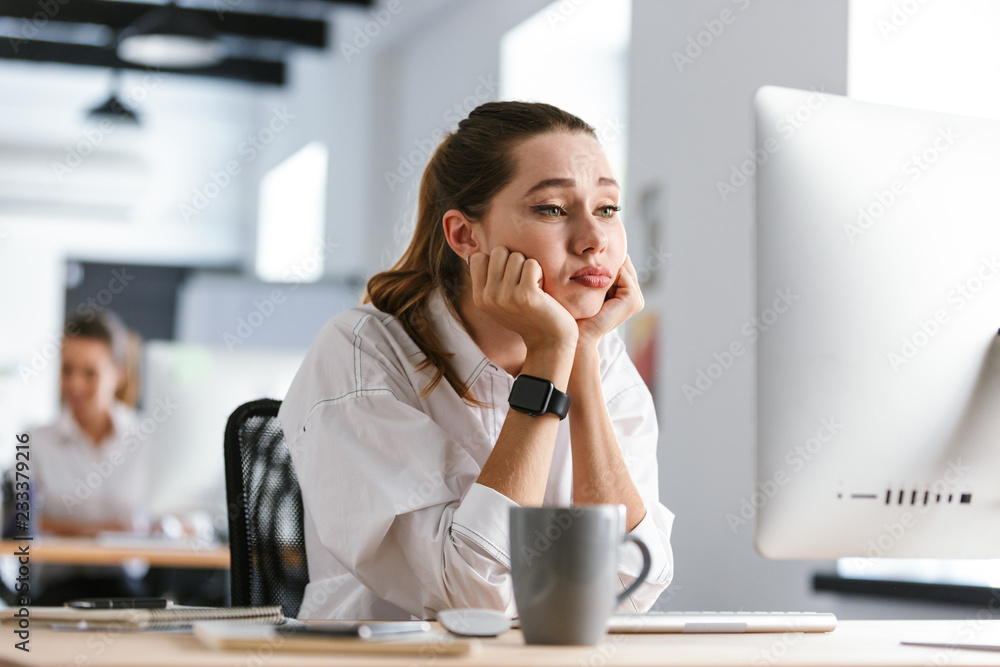 Fototapeta Bored young woman dressed in shirt sitting at her workplace