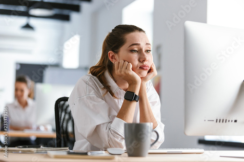 obraz PCV Bored young woman dressed in shirt sitting at her workplace