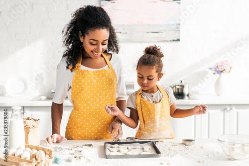 Photo african american mother and daughter looking at cookies on tray in kitchen