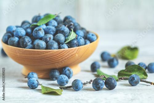 Valokuva Autumn harvest blue sloe berries on a light wooden table background