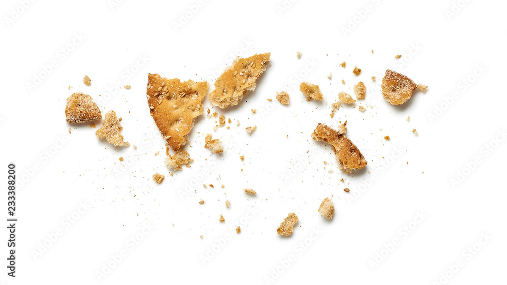 Fototapeta Scattered crumbs of cookie or cracker isolated on white background. Top view.